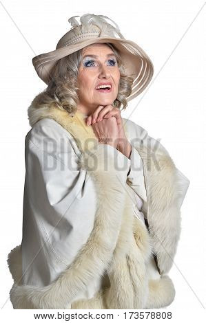 Senior woman in fur praying on white background