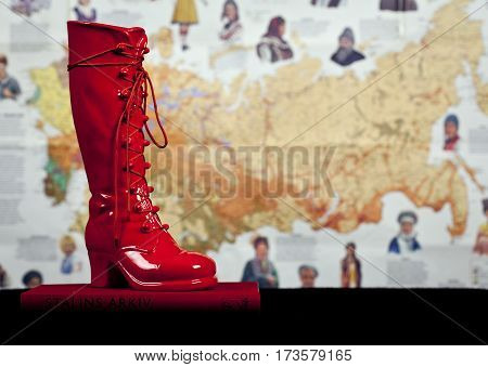 UMEA, SWEDEN ON DECEMBER 14. A red boot on a red book this side a fuzzy background on December 14, 2014 in Umea, Sweden. Black bookshelf. Illustrative Editorial.