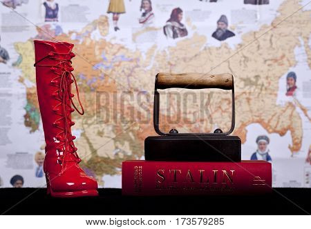 UMEA, SWEDEN ON DECEMBER 14. A red boot, red book under an old iron this side a fuzzy background on December 14, 2014 in Umea, Sweden. Black bookshelf. Illustrative Editorial.