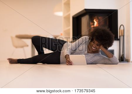 beautiful young black women using tablet computer on the floor of her luxury home in front of fireplace at autumn day