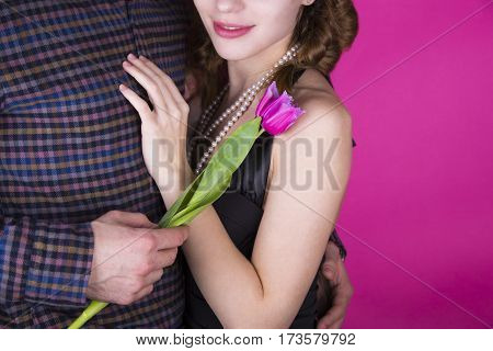 Beautiful young romantic couple with tender bouquet of pink and white tulips on bright crimson background