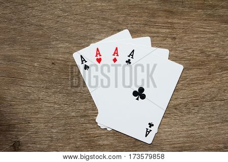Four card of ace on wooden background