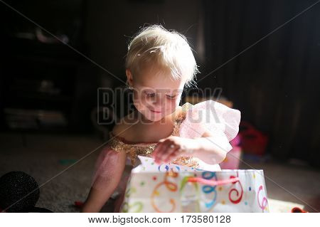 Happy Two Year Old Baby Girl Opening Birthday Presents