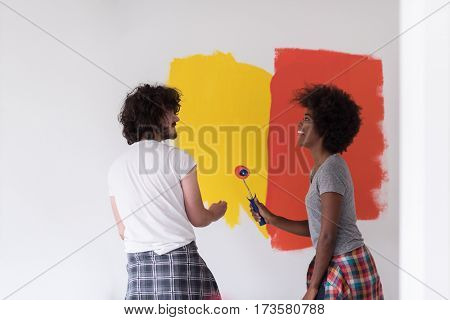 happy young multiethnic couple painting interior wall of new house