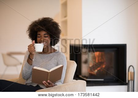 african american woman drinking cup of coffee reading book at fireplace. Young black girl with hot beverage relaxing heating warming up. autumn at home.
