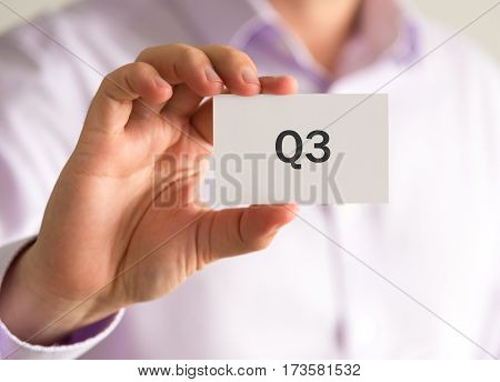 Businessman Holding A Card With Q3 Quarter 3 Message