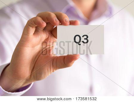 Businessman Holding A Card With Q3 Quarter 3 Message