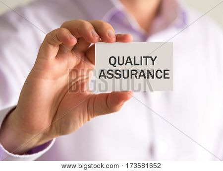 Businessman Holding A Card With Quality Assurance Message