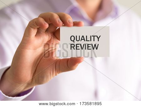 Businessman Holding A Card With Quality Review Message