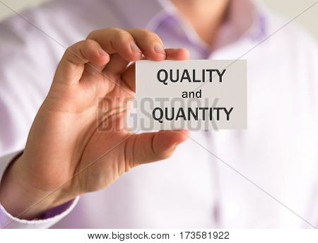 Businessman Holding A Card With Quality And Quantity Message