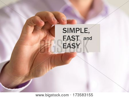 Businessman Holding A Card With Simple, Fast And Easy Message