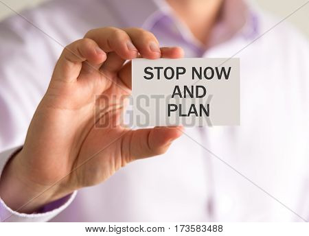 Businessman Holding A Card With Stop Now And Plan Message