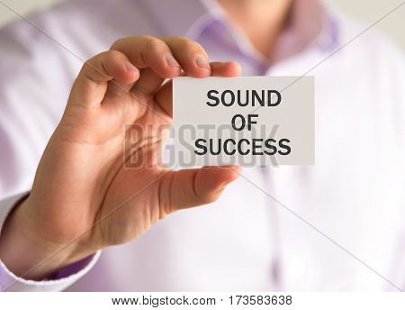 Businessman Holding A Card With Sound Of Success Message