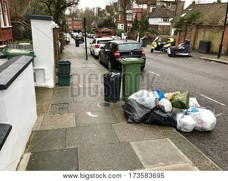 HAMPSTEAD - FEBRUARY 27, 2017: Bins and full plastic rubbish refuse bags piled high on the kerb in a street ready for collection day in Hampstead, North London, UK.