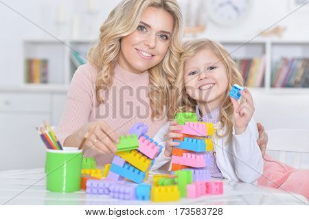 young mother and little daughter playing lego game poster