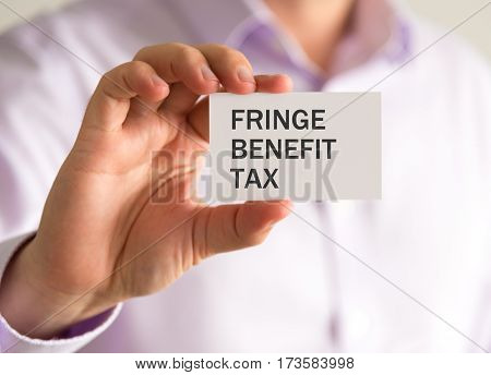 Businessman Holding A Card With Fringe Benefit Tax Message