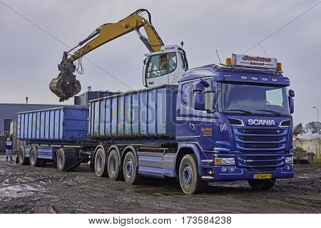 SNEEK, THE NETHERLANDS - MARCH 6, 2017: A mobile crane with hydraulic elevated cab and equipped with a sorting grapple is loading a container on lorry trailer with debris. Focus on first container.