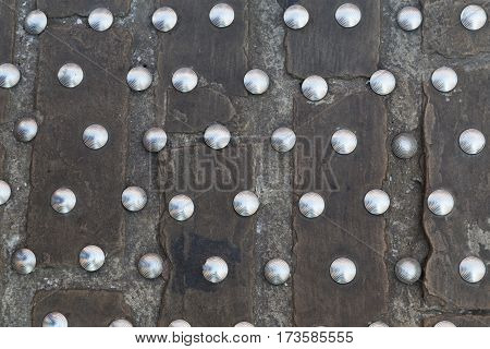 iron rivets on the stone cobbles close up - texture