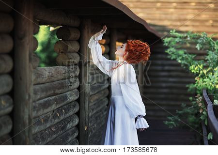 Beautiful red-haired barocco girl with a high hair in an old white dress in the park. The Victorian era. Historic barocco costume. White Queen. Princess castle