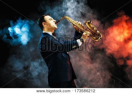 Elegant handsome man playing saxophone in studio against of blue and red smoke