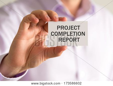 Businessman Holding A Card With Project Completion Report Message