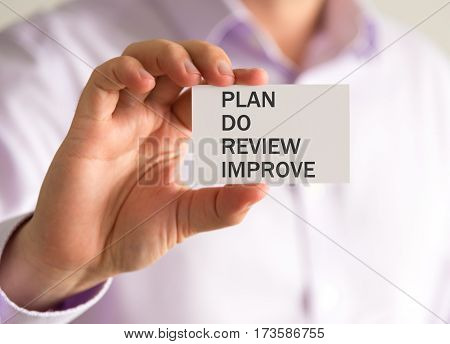 Businessman Holding A Card With Plan Do Review Improve Message