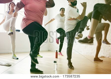 People exercising with trainer in training room