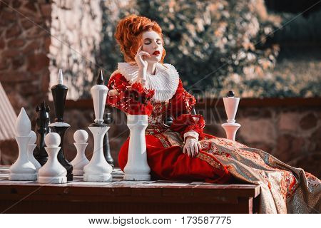 The Red Queen is playing chess. Red-haired woman in a chic vintage dress. Queen fashion photo play chess