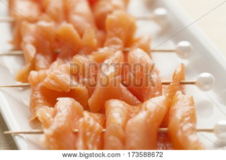 Smoked salmon on cocktail picks with a pearl as a festive snack