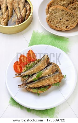 Sandwich with sprats on white plate top view
