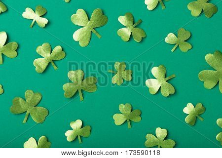 Paper clovers scattered over green background, top view