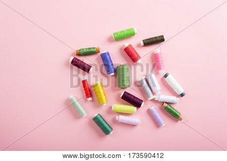 Colorful spools of thread over pink background, top view