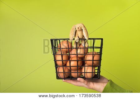 Small toy rabbit in a basket with brown chicken eggs hold on hand over green background