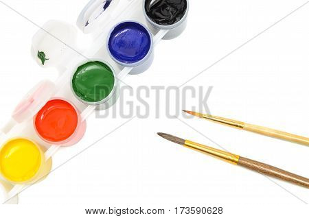set of gouache paints and brushes to paint on a light background