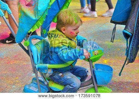 TULA RUSSIA - JUNE 13 2016: Small child in pram at festival of colors Holi on June 13 2016 in Tula Russia