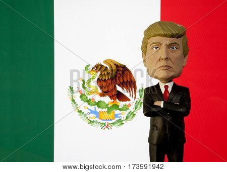 Donald Trump Bobble Head figure standing in front of a Mexican Flag