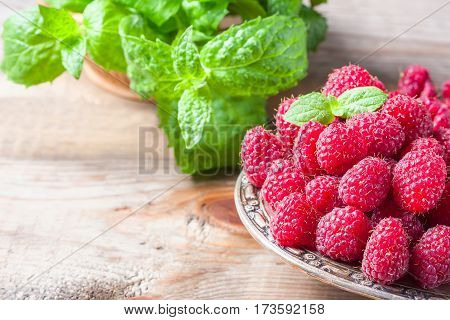 Ripe Sweet Raspberries In Bowl On Wooden Table, Closeup.