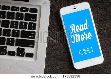 """Read More"" words on smartphone with a laptop near it - website multimedia and business concept"