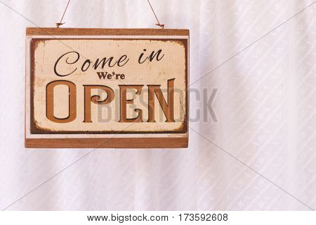 """Brown Wooden Vintage Sign with the word """"Open"""" in front of the coffee shop"""