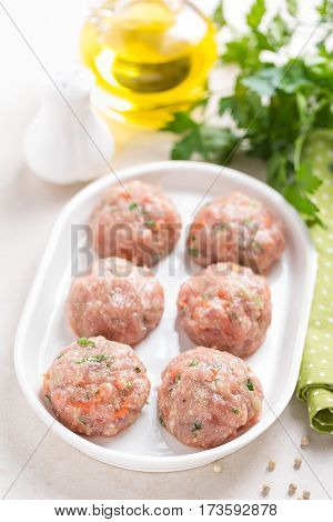 Raw meatballs on white plate cooking in kitchen