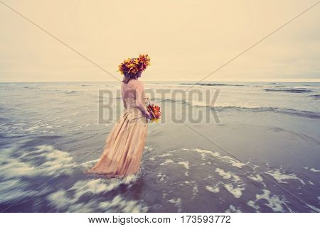 Woman walking into water in autumn with maple leaf crown