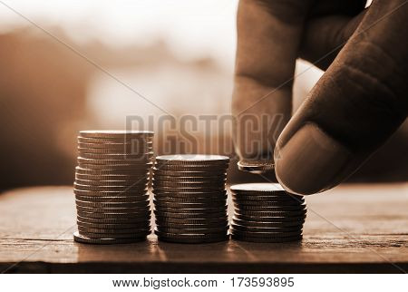 Hand with rows of coins and account for finance and banking concept Saving money concept
