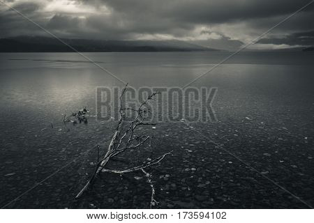 Image of a calm lake on a cloudy day.