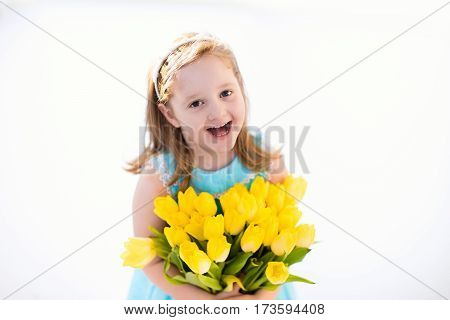 Cute little girl in blue dress holding tulip flowers bouquet on birthday party. Spring and Easter decoration. Child with yellow flowers. Kid with spring blossoms on christening celebration.
