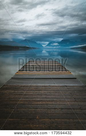 Image of a lake dock overlooking a reflective lake.