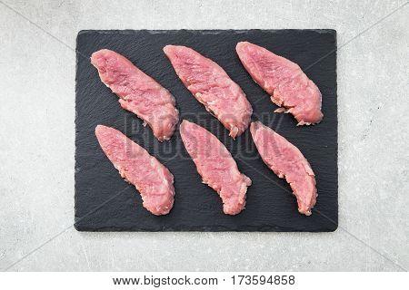 Raw Pork Meat On A Slate Board, On A Stone Background