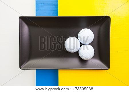 Black ceramic dish with golf equipment over white blue and yellow wooden table rectangle dish