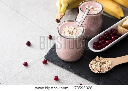 Smoothie Of Banana And Cranberries With Yogurt And Oats On An Slate Board