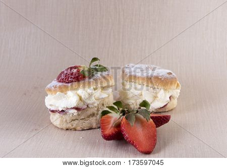 Two cream and strawberry jam scones with sliced strawberries