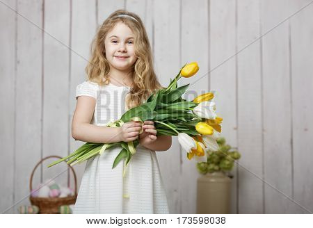 Portrait of cheerful little blonde girl with tulips bouquet on white wood background.